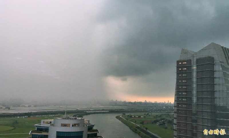 北市22日下起午後雷陣雨,從內科辦公大樓,清晰可見雨帶移動覆蓋市區。(記者張嘉明攝)