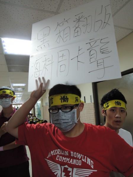 學生高舉抗議看板。(記者蔡清華攝)