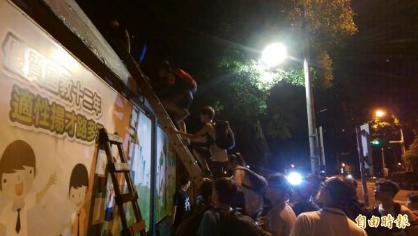 反黑箱課綱的學生們,今晚以木梯攀牆闖入教育部。(記者蔡穎攝)