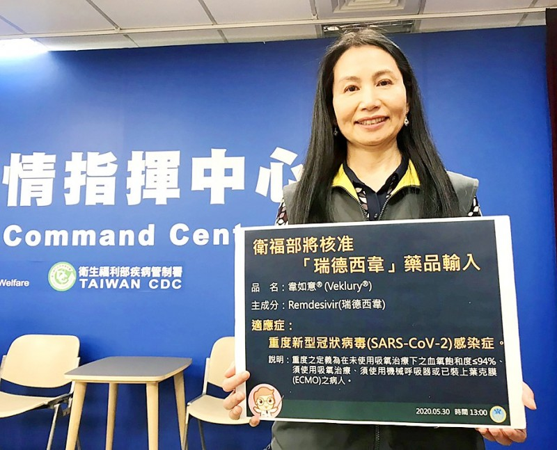 Food and Drug Administration Director-General Wu Shou-mei, who is also deputy head of the Central Epidemic Command Center's (CECC) research team, holds a sign at the CECC's daily briefing in Taipei yesterday explaining that the Ministry of Health and Welfare would approve imports of remdesivir. Photo: CNA