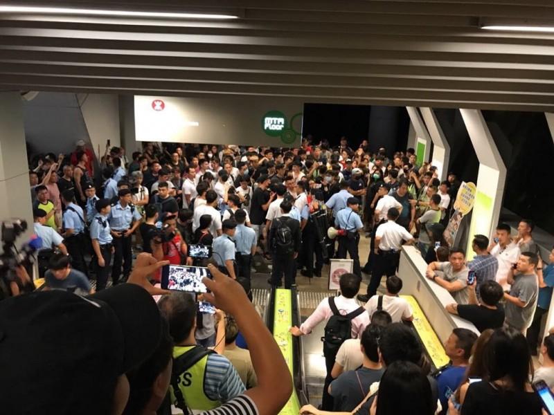 10日晚間,位於香港九龍區的港鐵油塘站有多名男子包圍想設置藍儂牆的年輕人且出言辱罵,引發高度緊張。(圖擷取自TG)