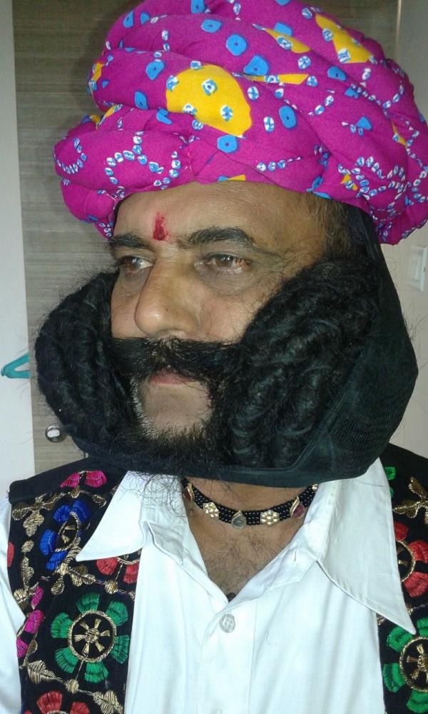 印度58歲的男子吉哈(見圖),留了長達6.7公尺的鬍子,打破世界紀錄。(圖擷取自Facebook)