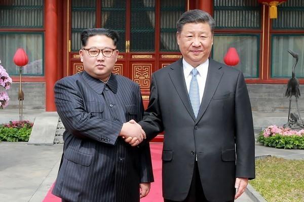 圖為北韓領導人金正恩(左)、中國國家主席習近平(右)。(法新社)