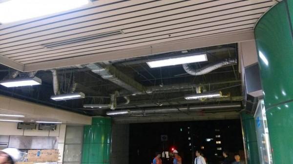 被吹垮的天花板,僅剩下燈架還掛在上投,一旁的售票機也被天花板砸毀。(圖擷自台北捷運臉書)