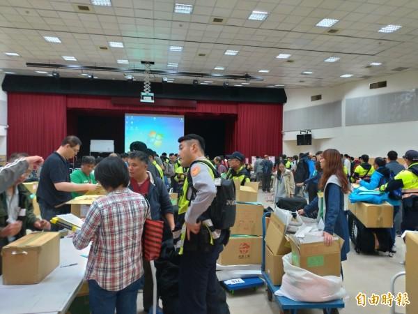 台北市各行政區選務人員陸續將投完的選票,送回信義區的北市選舉委員會放置,選務人員排隊等著簽到,深夜時分仍相當忙碌。(記者蔡亞樺攝)