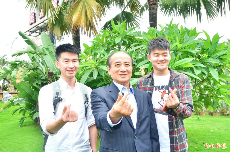 Chinese Nationalist Party (KMT) Legislator-at-large Wang Jin-pyng, center, and two members of his team make the heart sign in Tainan on Friday.   Photo: Wu Chun-feng, Taipei Times
