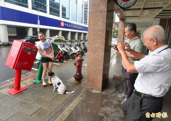 颱風蘇迪勒襲台,台北市龍江路郵筒遭掉下的招牌擊中變形,有民眾特替前來跟郵筒拍照。(記者王藝菘攝)