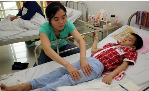 男童母親正在幫他按摩大腿。(擷取自重慶晨報)