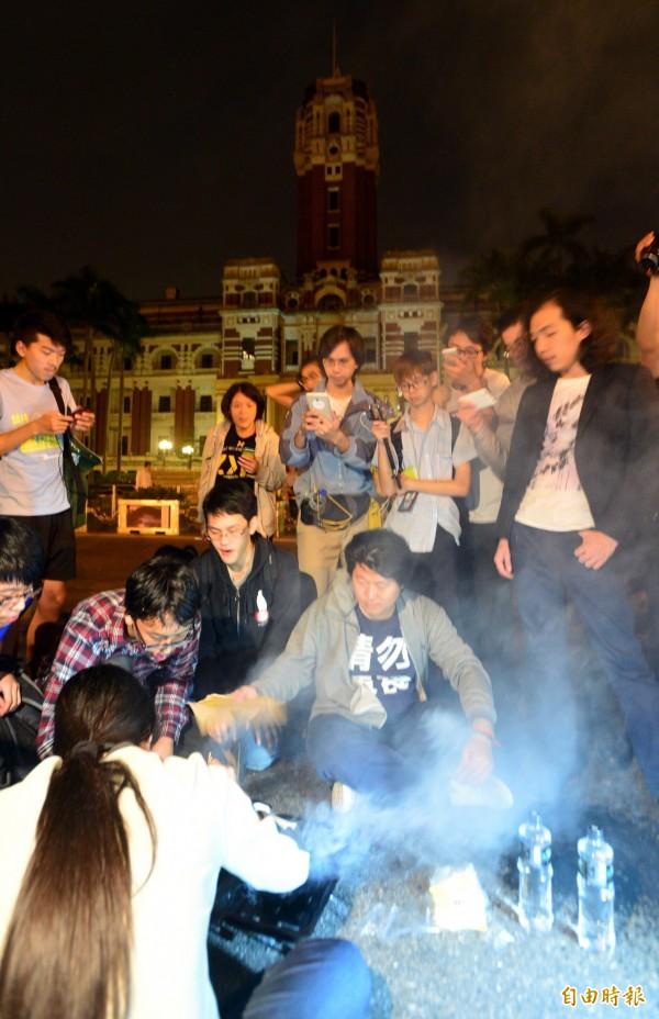 黑色島國青年陣線、民主鬥陣等30多個學生團體成員赴,總統府前抗議草率加入亞投行,一日凌晨仍然持續靜坐在總統府前,還有人在凱道前生火烤肉。(記者王藝菘攝)