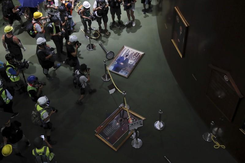 立法會大樓內的示威者將立法會歷任主席照片拆除並破壞。(美聯社)