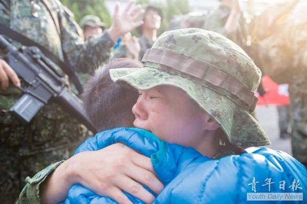 藍姓女士官的稚兒在一群身穿迷彩綠的大人中看到媽媽後,立刻跑過去擁抱媽媽,母子倆當場相擁而泣,感動所有在場的人。(圖擷自《青年日報》臉書)