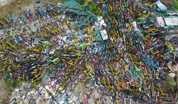 江蘇杭州最近因為共享單車數量過盛,在一處空地形成「單車公墓」,遭當地民眾批評「浪費資源」。(圖擷取自新華網)
