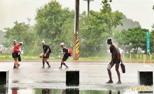 台北地區傍晚5點多降下驟雨,雨勢伴隨雷擊聲落下,一群在河堤外運動的學生用塑膠袋包住頭離去,全身被大雨淋到狼狽不堪。(記者羅沛德攝)