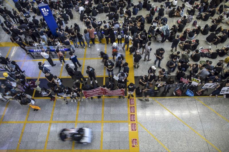 香港民眾在機場內拉起標語,要讓國際旅客知道香港發生什麼事情。(彭博)