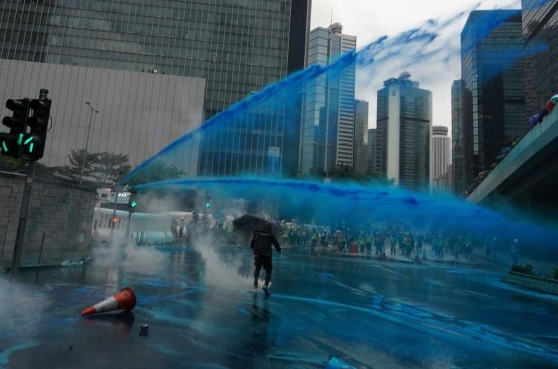 水砲車首度噴出藍色水柱,香港警方表示,將以示威者身上殘留的顏料作為日後拘捕的依據。(美聯社)