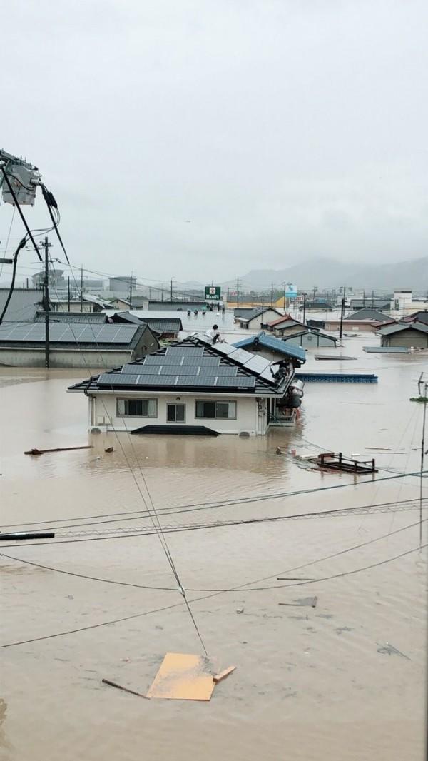 日本倉敷市真備町今(7日)多處民宅遭到淹沒,不少民眾爬上屋頂求救。(圖擷自@sou_frxmlf推特)