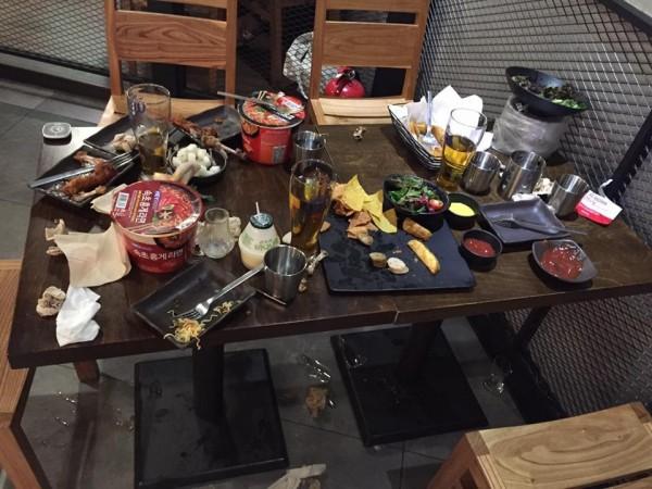 中客在店內桌面留下泡麵等一片狼藉,桌下還有摔碎的玻璃杯。(圖擷自爆料公社)