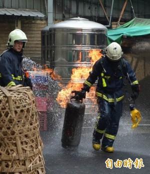 瓦斯桶狂噴火 消防員冒險拖到戶外