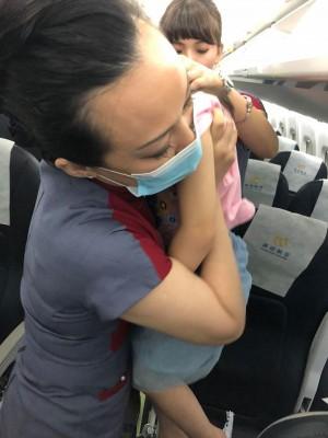 母搭機「1打2」手忙腳亂 空姐暖助抱孩獲好評