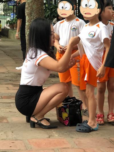 幼稚園老師蹲下幫小孩整理儀容  展露「成人」身材引暴動