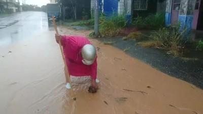泥流淹路面 婦人自行清除落葉斷枝防淤塞
