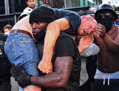 照片網路瘋傳!倫敦非裔壯漢扛受傷白人 英國抗議背後藏暖心故事
