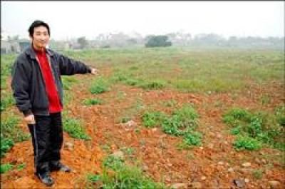 新坡國小家長會長吳慶昌指著一大片休耕農地說,這就是他們社區及小球員的棒球夢田所在。(記者陳文正攝)