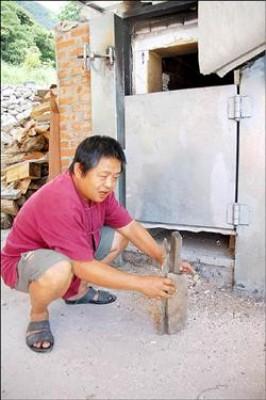 廖光亮將窯口改為上下雙門式,添柴不必門戶大開,堆柴也改直堆法。(記者黃明堂攝)