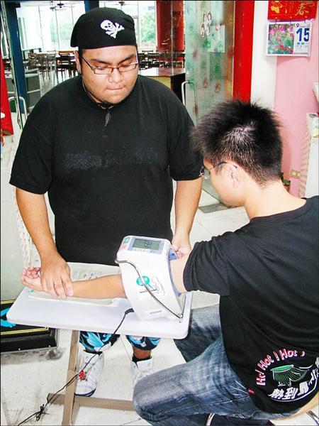 元智大學外籍生雷傑(左)擁有瓜地馬拉護理師的證照,下課後也會到衛生保健室工讀。台灣不承認瓜國學歷,他謹守分寸,只幫忙量血壓等簡單的工作。(記者羅正明攝)