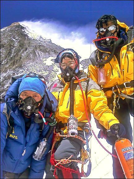 七頂峰登山隊黃致豪(左起)、江秀真與伍玉龍,在第三營前戴氧氣罩準備出發,後方是珠峰。(歐都納提供)
