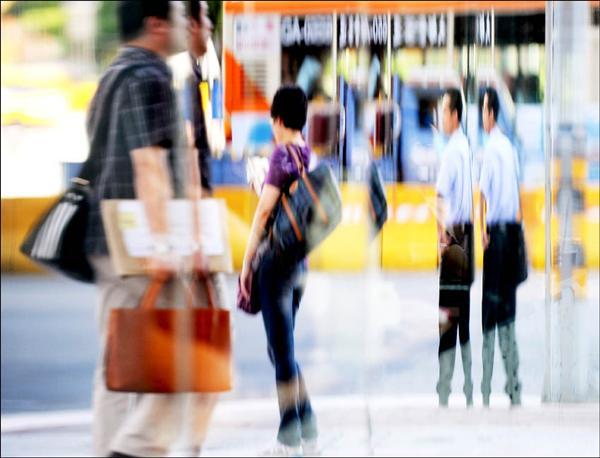 七月份失業率與上半年薪資減幅,均創歷來新高。大樓落地窗裡上班族模糊的身影,似乎象徵了人心不安。(記者羅沛德攝)
