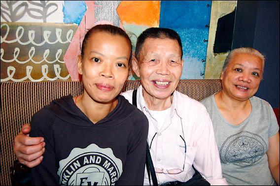 抱著大病初癒的女兒,劉父(中)放心的露出笑容。(記者何玉華攝)