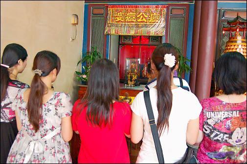 昨天是七夕情人節,有不少女性到彰化市開化寺向痘公、痘婆求美貌祈姻緣。(記者湯世名攝)
