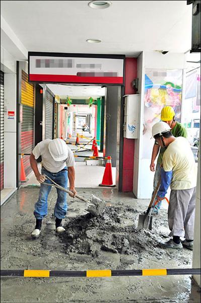 嘉義市政府辦理中山路騎樓整平工程,包商一早趁店家還沒開門時施工,降低對週遭商店的影響。(記者余雪蘭攝)