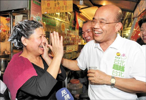 民進黨台北市長參選人蘇貞昌(右)昨晚參加中崙市場慈賢宮普度活動,一位熱情民眾顧不得頭洗一半,衝出美容院表達支持。(記者簡榮豐攝)