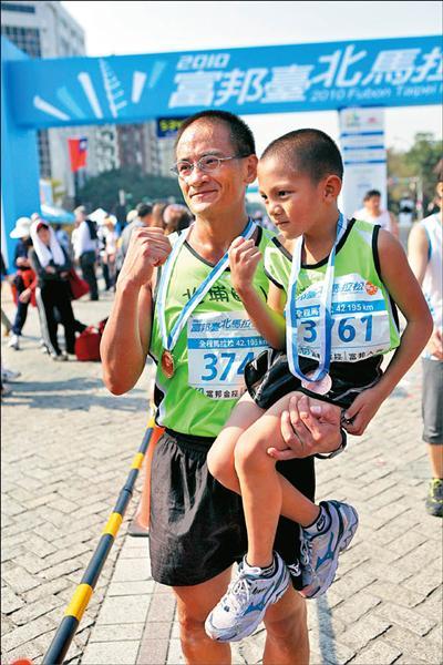 年僅六歲的吳均浩(右)是昨日二○一○富邦台北馬拉松最年輕的完賽選手,跆拳道教練阮漢魁則一手抱著辛苦完賽的愛徒。(記者龍柏安攝)