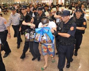 被菲律賓送往中國的我國籍十四名詐欺犯,幾經周旋,終於在今日下午自北京押解返台。(記者姚介修攝)