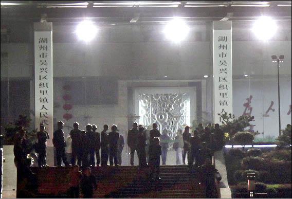 中國浙江湖州織里鎮的鎮政府大門外,二十七日晚間仍有鎮暴警察駐守,中國官方宣稱該起抗稅騷亂事件已經獲得控制。(路透)
