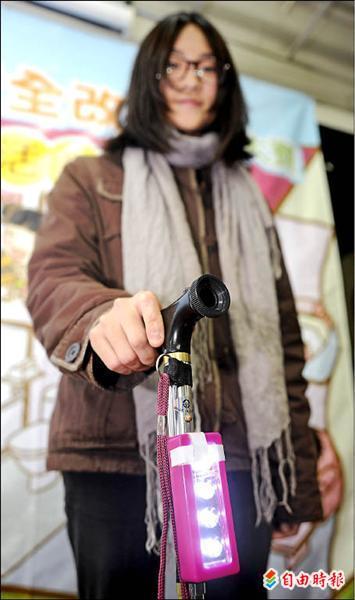 東吳大學周沂潔展示「發光的枴杖」,讓老人家可以走到哪就亮到哪。(記者劉信德攝)