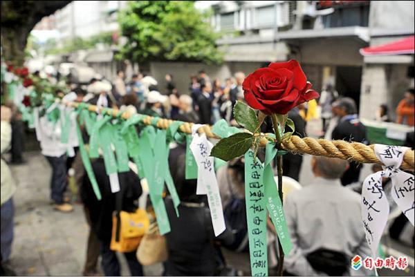 鄭南榕紀念館昨天舉辦鄭南榕殉道廿三週年追思會,出席民眾在「自由巷」繫絲帶緬懷。(記者簡榮豐攝)
