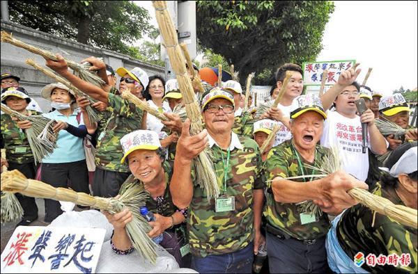 來自嘉義的民眾組成「反漲義勇軍」,昨在凱道上演行動劇,義勇軍拿著掃帚充當長槍對準總統府,要將總統馬英九轟下台。(記者劉信德攝)