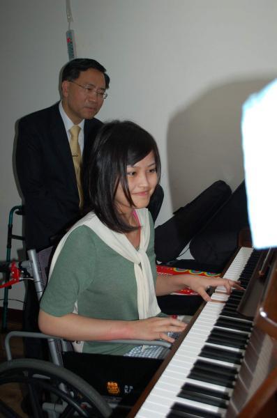 癱瘓18個月的台中女中學生莊品瑄(右),今天在台中市副市長蔡炳坤等人面前彈奏鋼琴,恢復狀況讓大家頻稱「奇蹟」。(記者陳建志攝)