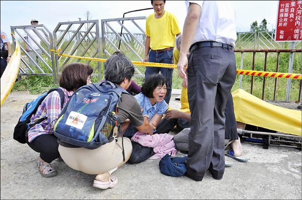 張森文的太太彭秀春癱軟在地,灣寶社區發展協會理事長洪箱等人在旁安撫。(記者彭健禮攝)