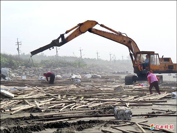 蚵民雇怪手忙著回收堪用的棚架,以減少損失。(記者蔡文居攝)