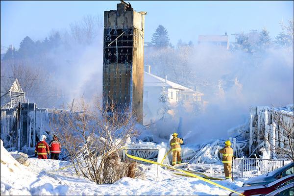 發生大火的安養院在23日早上火勢撲滅後,還冒出陣陣濃煙,消防人員冒著攝氏零下20度的低溫,在殘骸中搜救可能的生還者,期盼出現奇蹟。(法新社)