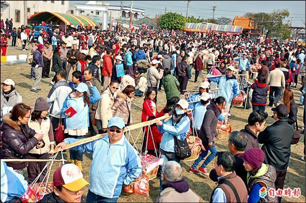 東勢鄉昌南村吃飯擔,依傳統由居民挑飯擔進入會場。(記者林國賢攝)