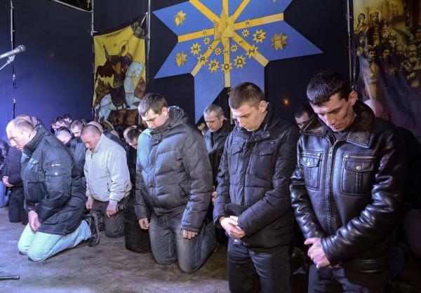 烏克蘭鎮暴警察昨天部分警員出現在西部城市利沃夫(Lviv),集體下跪請求原諒。(路透)