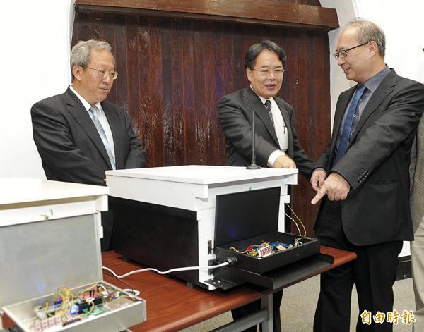 台大教授楊恩誠(右)與江昭皚( 中)昨日公布蜜蜂大量減少原因的研究報告,並展示計算蜜蜂返回蜂箱的紅外線計數器材。(記者王敏為攝)