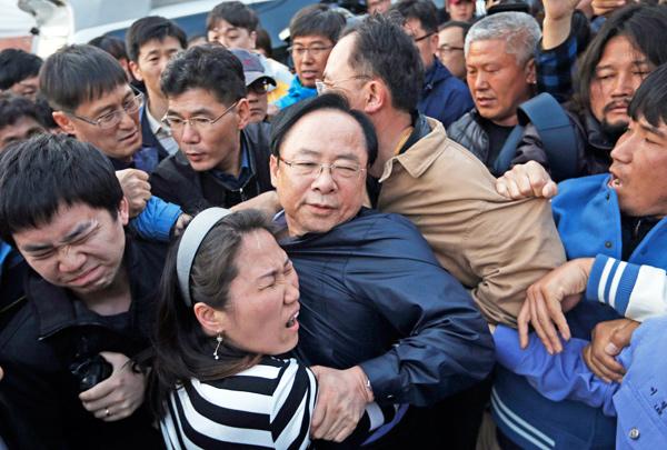 ▲南韓海洋水產部長官李柱榮20日赴珍島探視「歲月號」罹難者家屬,遭憤怒家屬推擠。(路透)