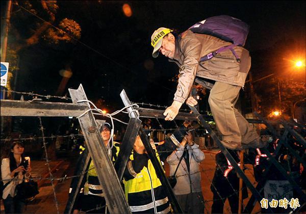 民眾在公投盟總召蔡丁貴(右)號召下,昨晚試圖推翻拒馬進入警方封鎖區,帶頭的蔡丁貴隨即被警方逮捕。(記者王敏為攝)